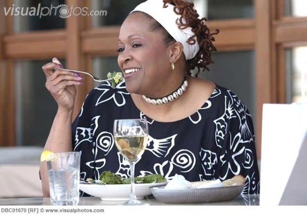 African woman eating salad in cafe